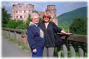 Linda has her arm around Donna's shoulder as they stand on a bridge in front of a stone castle.  Leafy hillsides are in the background.
